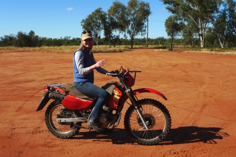 Volunteer learning to ride motorbike.